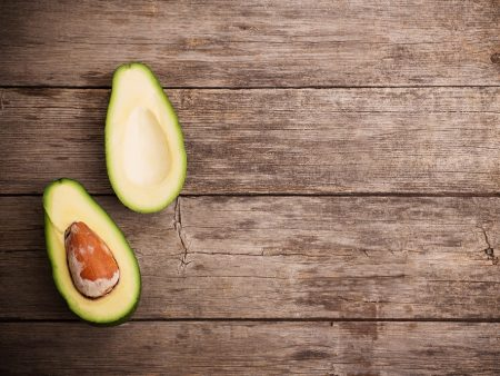 Ripe avocado on a wooden background