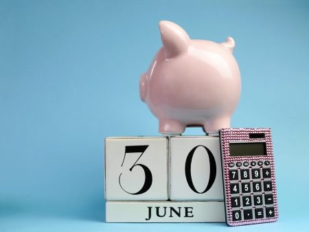 Calendar date for End of Financial Year, 30 June, for Australian tax year or retail stocktake sales, with piggy bank and pink calculator on sky blue background, with copy space.