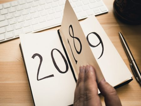 New Year 2019 is coming concept. Female hand flips notepad sheet on wooden table. 2018 is turning, 2019 is opening