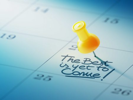 Concept image of a Calendar with a yellow push pin. Closeup shot of a thumbtack attached. The words The best is yet to come written on a white notebook to remind you an important appointment.